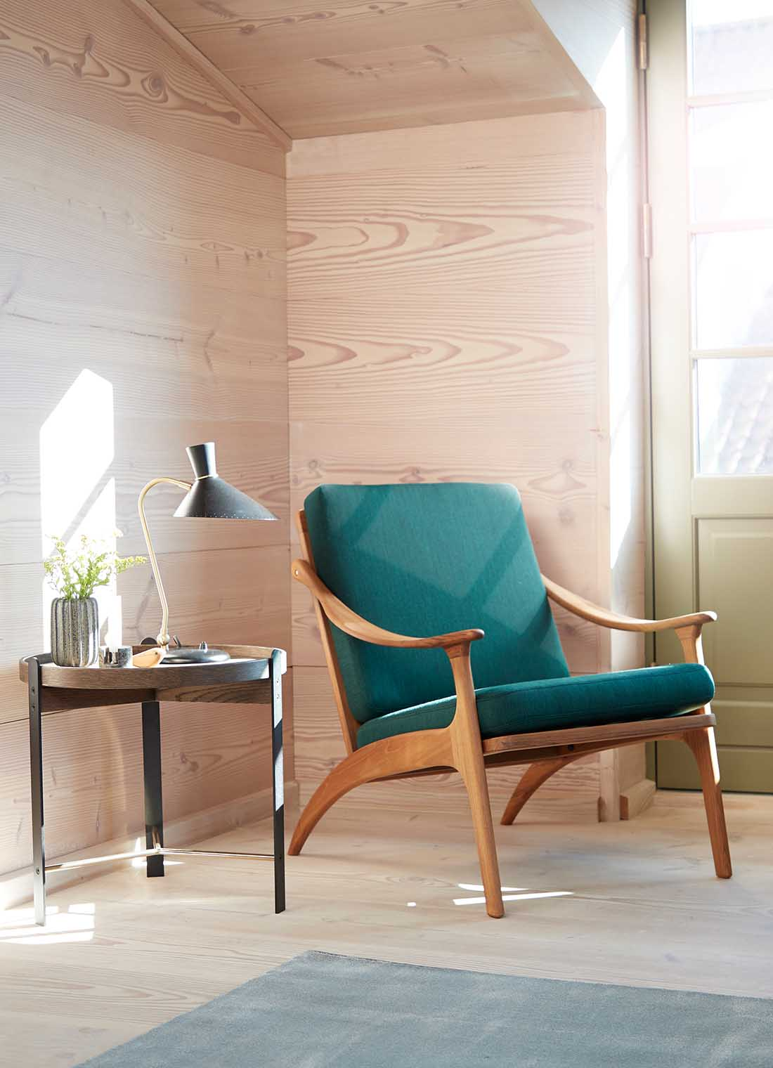 Lean Back lounge chair in teak wood and forest green in a light, modern room with Compose side table.